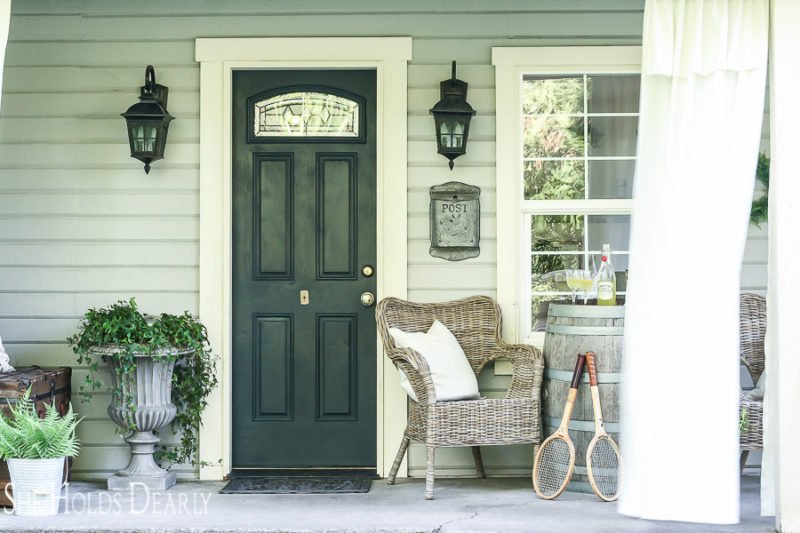 navy front door, wicker chairs, patio curtains, outdoor curtains, whiskey barrel as porch decor