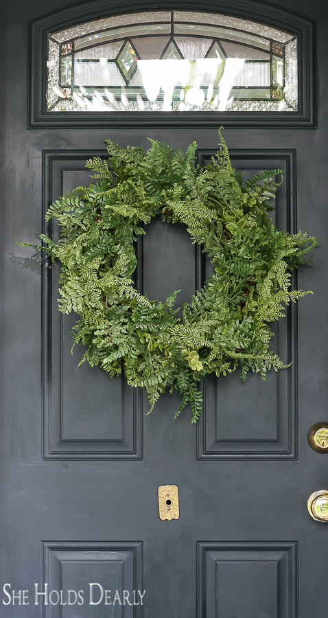Faux fern wreath on navy blue front door
