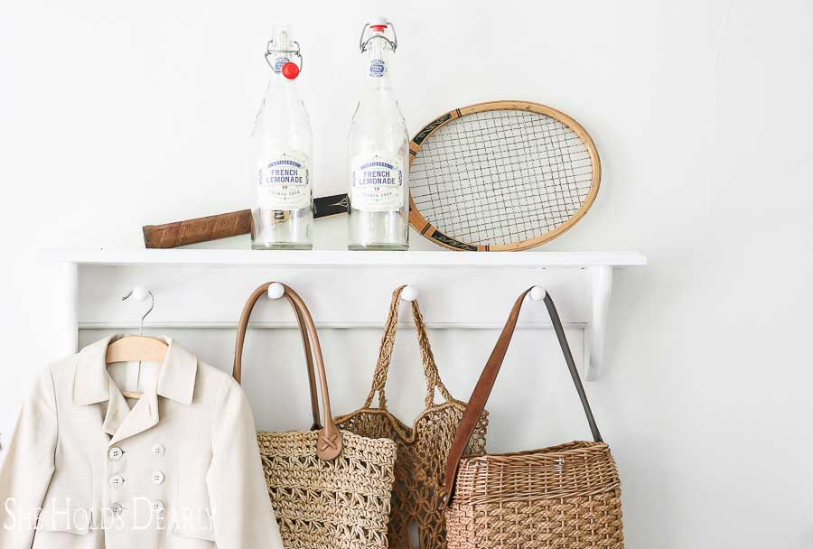Vintage tennis racket and french lemonade on shelf above coat rack